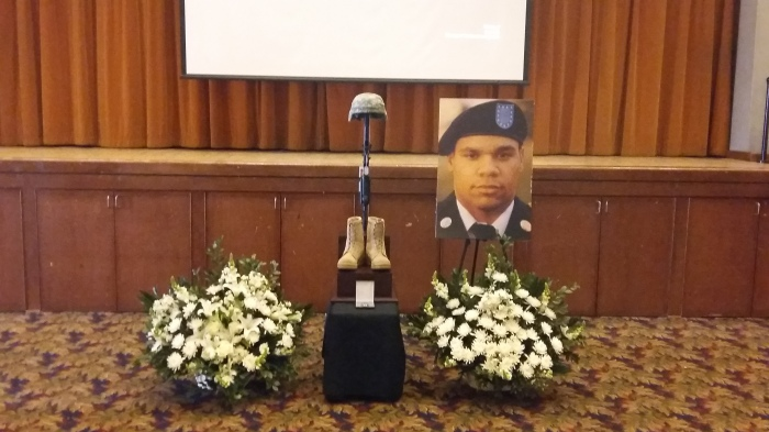 The Memorial Stand is set with a rifle, helmet, boots and dog tags. The Soldiers' final award and photo are also on display (photo by Daryl Densford)